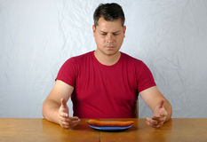 Young man dislike carrot on plate Stock Images