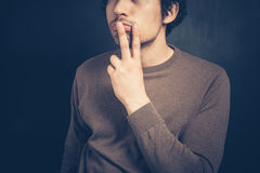 Young man displaying obscene gesture. Young man is displaying an obscene gesture Royalty Free Stock Image
