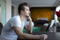 Young man distract attention away from work on laptop. Young casual man distract attention away from work at laptop Royalty Free Stock Images