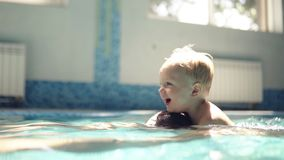 Young man dives under the water. Rowing in the closed swimming pool. Little boy is onhis fathers back. Smilling. Mother. Is hugging them. Happy family time stock video