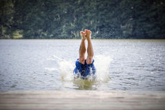 Young man diving into a lake. Careless and risky water jump. Summer vacation dangerous outdoor activity royalty free stock image
