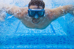 Young man in diving mask swimming the front crawl in a pool, tak Stock Images