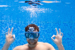 Young man in diving mask swimming the front crawl in a pool, tak. En under water, summer party Royalty Free Stock Photo