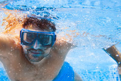 Young man in diving mask swimming the front crawl in a pool, taken under water. Summer party royalty free stock images