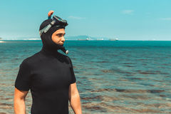 Young Man In Diving Suit Goes To Sea In Summer Outdoors. Young man in diving suit with mask and snorkel, goes to sea in summer outdoors Stock Photo
