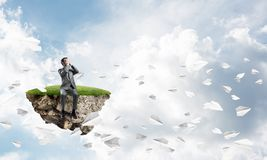 Young man do not want to see anything and paper planes fly around Royalty Free Stock Photo