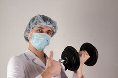 Young man doctor keep dambbell in a hand and show like on neutral background. Medcine and sport concept. Stock Image
