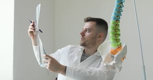 Portrait of young man doctor surgeon is looking at x-ray image and explaining disease to patient. Young man doctor surgeon is looking at x-ray image and stock video