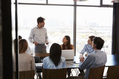 Young man with documents addresses team at boardroom meeting. Young men with documents addresses team at boardroom meeting Stock Image