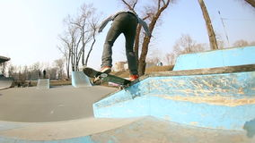 Young man does a trick on a skateboard in a skate park stock footage