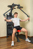Young man does workout at chest fly machine in gym Stock Image