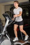 Young man does workout at elliptical trainer in gym Stock Images