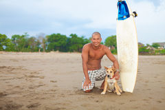 Young man and dog. Young man with surfboard and dog on beach Stock Image
