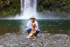 Young man and golden retriever reach the waterfall Stock Images