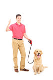 Young man with a dog giving thumb up Royalty Free Stock Image