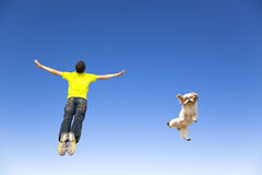 Young man and  dog jumping in the sky. Relaxing young man and  dog jumping in the blue sky Royalty Free Stock Photos