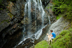 Young man with a dog near a waterfall stock images
