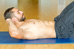 Young man doing abdominal crunches in gym Stock Images