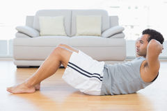 Young man doing abdominal crunches in the living room Stock Photo