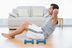 Young man doing abdominal crunches in the living room Stock Image