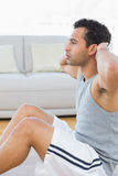 Young man doing abdominal crunches in the living room Royalty Free Stock Photo