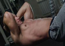 Young man doing abdominal exercises Royalty Free Stock Photography