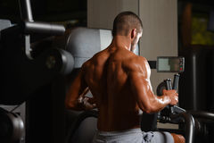 Young Man Doing Back Exercise On A Machine Royalty Free Stock Image
