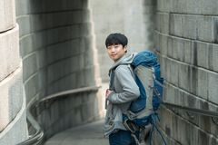 Young man doing a backpacking trip in a Korean traditional castle wall. A young man doing a backpacking trip in a Korean traditional castle wall stock photo