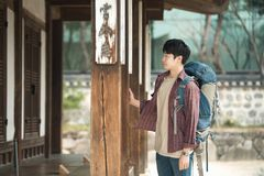 Young man doing a backpacking trip in a Korean traditional house. A young man doing a backpacking trip in a Korean traditional house stock photos