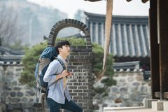 Young man doing a backpacking trip in a Korean traditional house. A young man doing a backpacking trip in a Korean traditional house royalty free stock photo