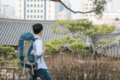 Young man doing a backpacking trip in a Korean traditional house. A young man doing a backpacking trip in a Korean traditional house stock images