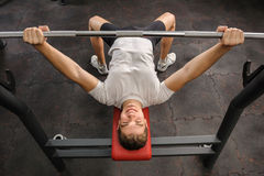 Young man doing bench press workout in gym Royalty Free Stock Images