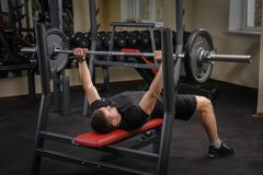 Young man doing bench press workout in gym Royalty Free Stock Photography
