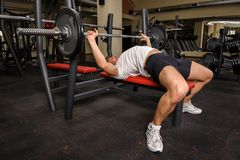 Young man doing bench press workout in gym. Handsome young man doing bench press workout in gym Royalty Free Stock Image