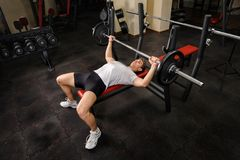 Young man doing bench press workout in gym Stock Images