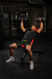 Young man doing bench press workout in gym Stock Photography