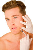 Young man doing botox injections. On white background Royalty Free Stock Photo
