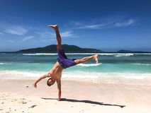 Young man doing a cartwheel at a tropical beach in Seychelles royalty free stock photography