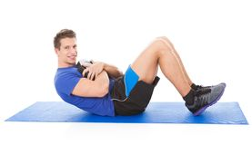 Young Man Doing Crunches. Portrait Of Young Man Holding Weight Doing Crunches Over White Background Stock Image