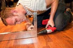 Young man doing DIY home improvements. Bending down on a wooden floor drilling a hole into a metal bracket Stock Image