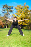 Young man doing exercise in autumn park Royalty Free Stock Photos