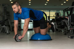 Young Man Doing Exercise On Bosu Balance Ball. Personal Trainer Doing A Exercise For Abs With Bosu Balance Ball As Part Of Bodybuilding Fitness Training Stock Photography