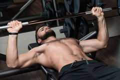 Young Man Doing Exercise For Chest With Barbell Royalty Free Stock Photo