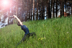 Young man doing exercise on the hill Stock Images