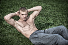 Young man doing exercises for abdominal muscles on green grass. Royalty Free Stock Photos