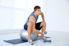 Young man doing exercises with dumb-bells and ball. On rug Royalty Free Stock Images
