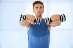 Young man doing exercises with dumb-bells. Indoors Royalty Free Stock Image