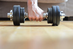 Young man doing exercises with dumbbells at home Royalty Free Stock Images