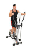 Young man doing exercises on elliptical cross trainer Royalty Free Stock Photos