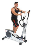 Young man doing exercises on elliptical cross trainer Stock Photo